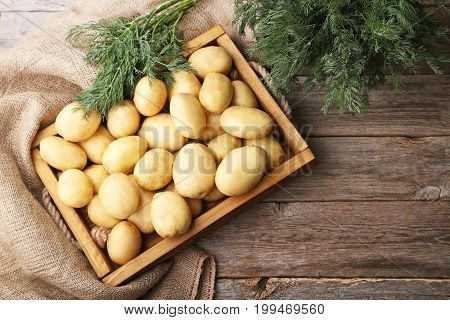 Potatoes In Crate With Dill On Grey Wooden Table