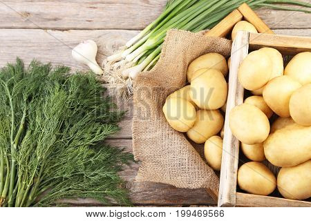 Potatoes In Crate With Dill, Onion And Garlic On Grey Wooden Table