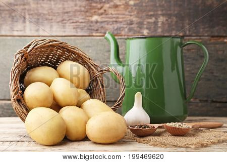 Potatoes In Wicker Basket With Pepper And Garlic On Wooden Background