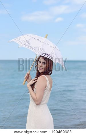 portrait of redhead woman at beach with umbrella