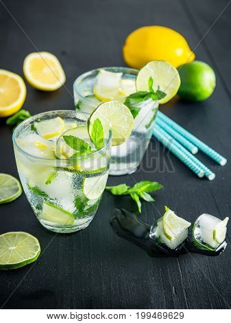 Refreshing cocktail with crushed ice and lame with lemon on dark background