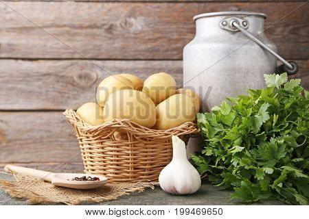 Potatoes In Wicker Basket With Parsley And Garlic On Wooden Background