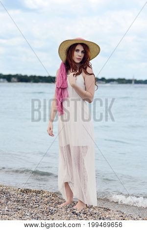 redhead woman with straw hat at the beach