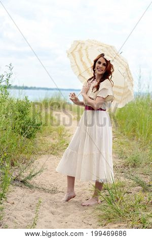 vintage woman with parasol on beach path