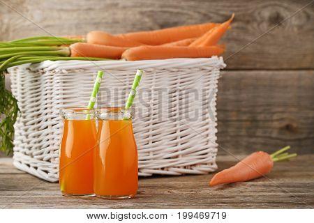 Fresh Carrot Juice In Bottles On Wooden Table