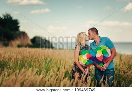 Kissing Couple In High Grass With Toy Windmill