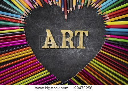 Education concept. Top view of crayon pencils shaped heart symbol with Art text