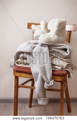 stack of warm clothes on the chair Pair of warm winter sheepskin slippers