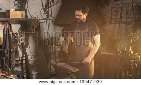 Man works with molten metal in the forge