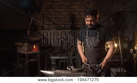 Portrait of a man of a blacksmith in the working atmosphere. Brutal man looks and smiles at the camera