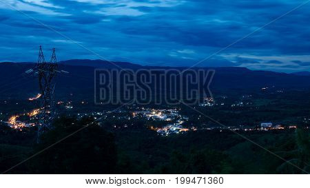 The big hight voltage pole and the city in countryside in the night.