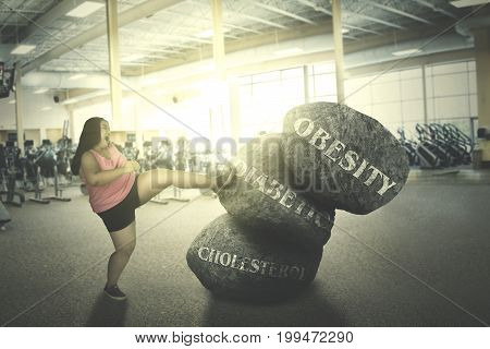 Fat woman exercising in the fitness center while fighting with her diseases shot at sunset time