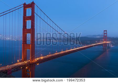 Night view at illuminated Golden Gate Bridge which spans Golden Gate strait at San Francisco Bay. California, USA