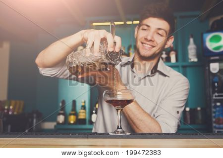 Young handsome bartender in bar interior pouring alcohol cocktail drink into glass. Service industry occupation.