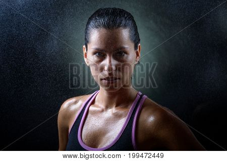 young sport woman portrait looking seriuously to the camera on a dark background in a challenge attitude