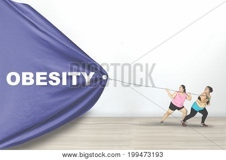 Two fat young women draw a big banner with Obesity text and wearing sportswear