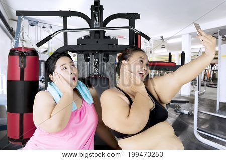 Two fat women using smartphone to take a selfie picture while exercising in the fitness center