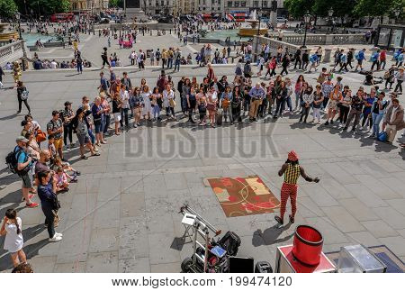 Trafalgar Square London UK - July 21 2017: Street performer with large crowd watching. Taken from the National Portrait Gallery looking down.
