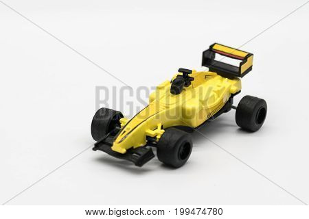 Yellow toy as formula car isolated on white background