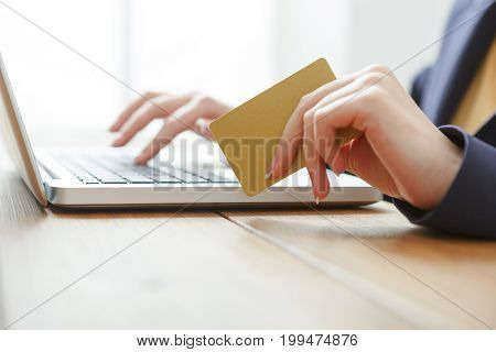 Online shopping in internet concept. Woman use credit card and laptop while sitting at wooden table, close-up, side view.