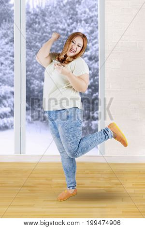 Picture of a joyful blonde woman with overweight body reading sms message on her cell phone near the window