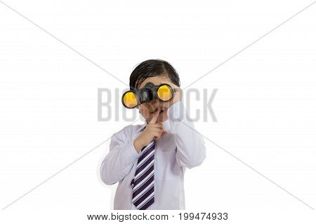 Picture of little cute boy is looking through a binocular while showing forefinger over lips isolated on white background