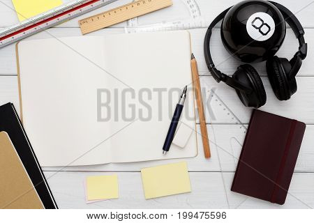Education and work concept, top view shot of workplace. Stationery supplies - blank notepad, pen, binder clips, ruler, paperclips and headphones on white wooden desktop, flat lay, copy space, mockup