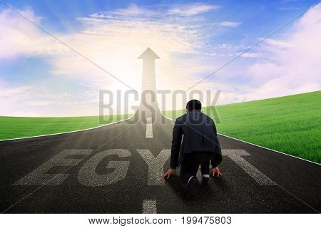 Young male manager in ready position to run toward arrow upward with Egypt word on the highway