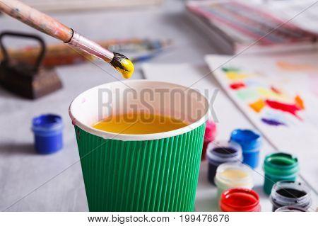 Hand washing brush, artist work background. Visual art concept