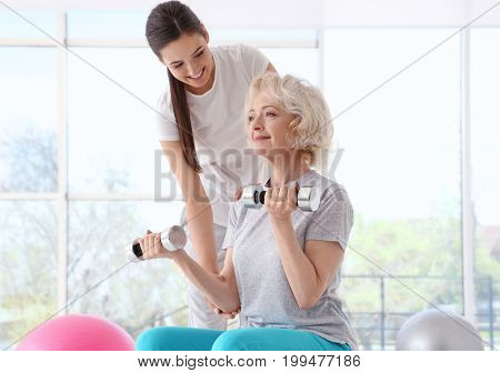Physiotherapist working with elderly patient in modern clinic