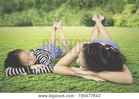 Picture of young mother relaxing with her daughter while lying down in the meadow