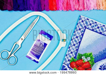 Colorful blue background of sewing items: scissors needles embroidery frame pallet of colorful threads and embroidery pattern. Embroidery and sewing concept