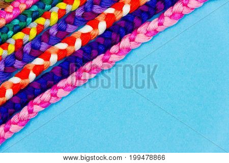 Colorful blue background of pink violet yellow green red purple knitted pigtail. Knitted concept