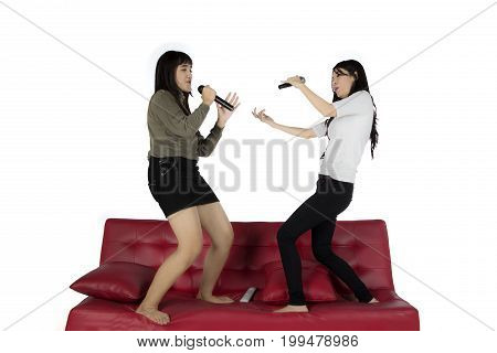 Portrait of two pretty multiracial girls singing karaoke while dancing on a sofa isolated on white background