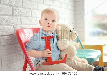 Cute little boy with letter L sitting on chair at home