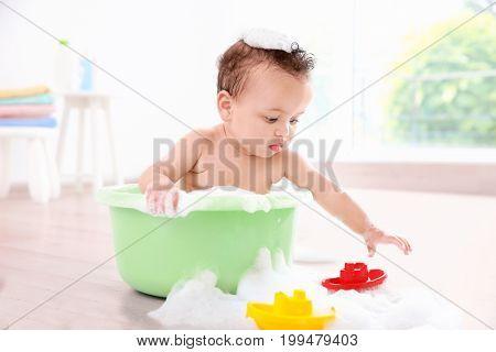 Little baby washing in bath basin at home