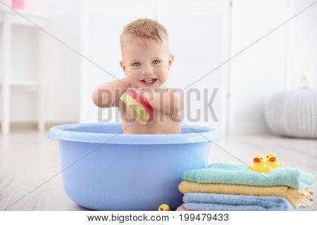 Little baby boy washing in bath basin at home