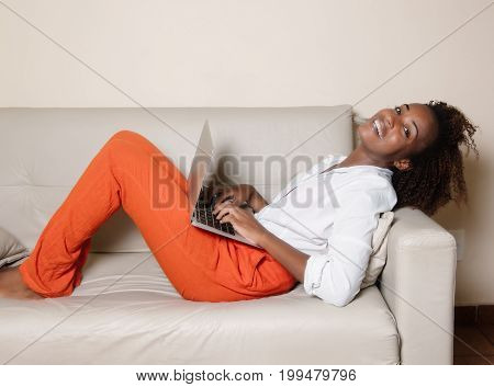 Laughing african american woman with notebook on couch