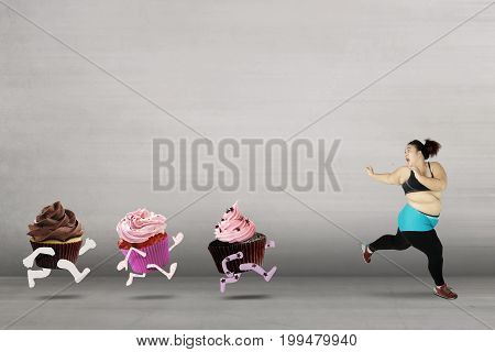 Diet concept. Obese woman evades from cupcakes with scared expression and refuse to eat cupcakes for lose weight