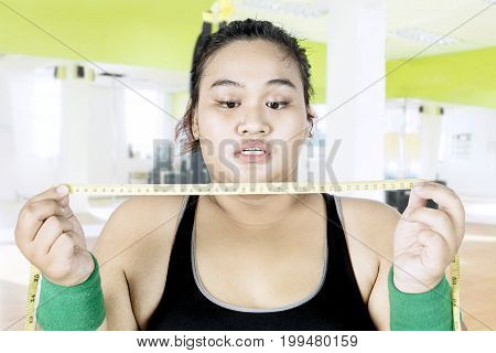 Obese woman feeling shocked while looking measuring tape in the fitness center