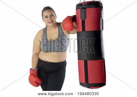 Portrait of a young overweight woman standing next to boxing bag while wearing sportswear and boxing gloves