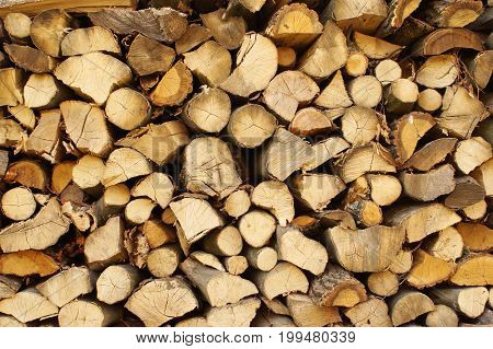 Chopped wood stacked in a woodpile. Solid ecological fuel for heating the house in winter frost. Renewable energy.