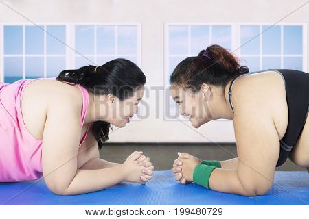 Two obese women doing plank exercise together on mattress in the gym