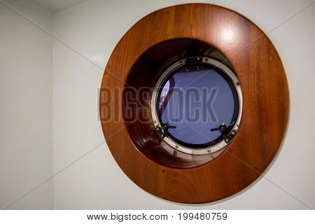 Close up picture of modern wooden porthole part of yaht interior