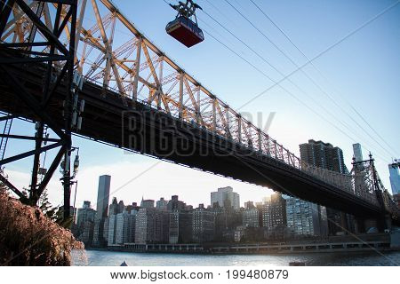 Queensboro bridge with trams over the river and Manhattan city before sunset