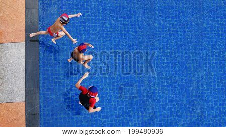 Two little boys and girl fun jumping into the swimming pool, Top view