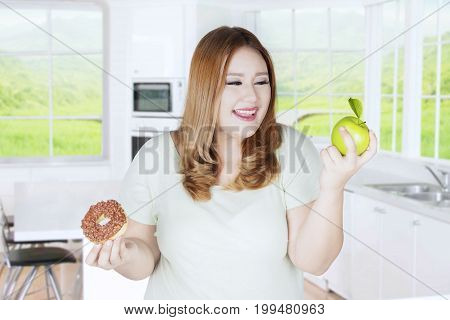 Portrait of overweight girl with blonde hair choosing between apple fruit or donut in the kitchen
