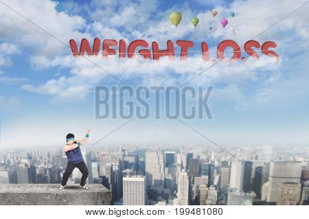 Image of overweight male standing on the rooftop while pulling text of weight loss on the sky
