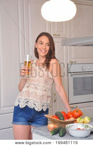 Beautiful smiling girl drink beer in the kitchen. Portrait of cute teenage girl drink cold drink
