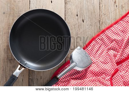empty pan with spade of frying pan and red tablecloth on wood background